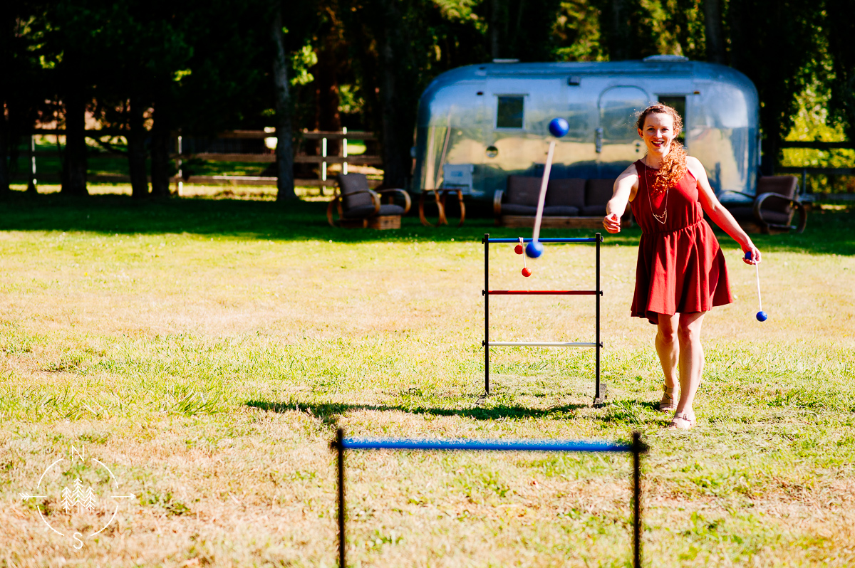 A wedding guest plays ladder ball with an Airstream Trailer in the background.