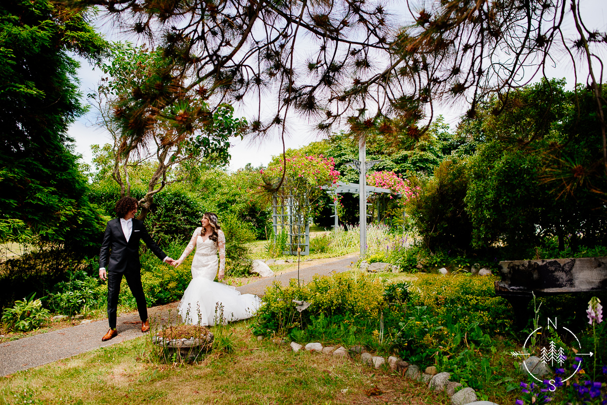 A bride and groom walk along the grounds of Crockett Farm in Whidbey Island.