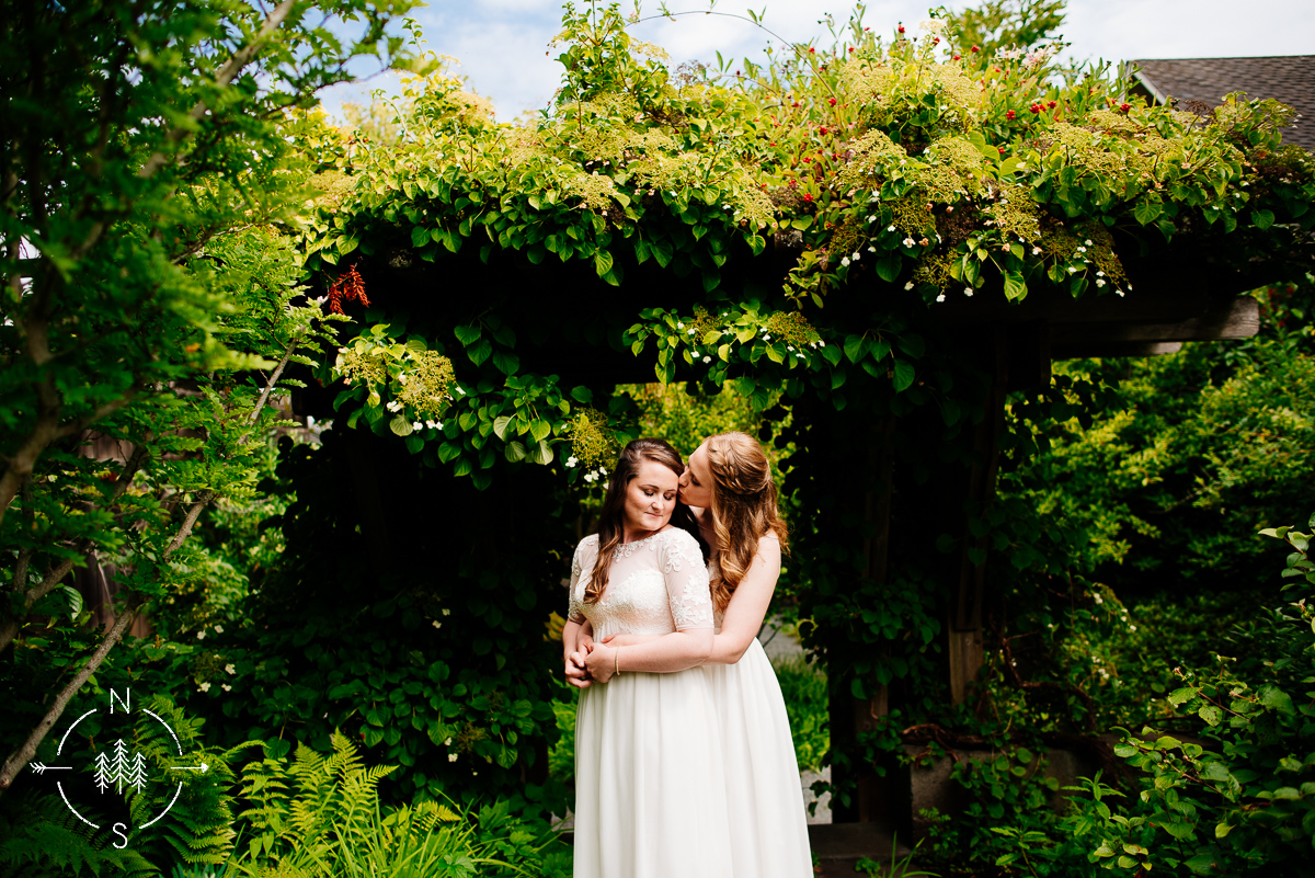 Two brides kiss in a lush garden at the Inn at Langley on Whidbey Island.