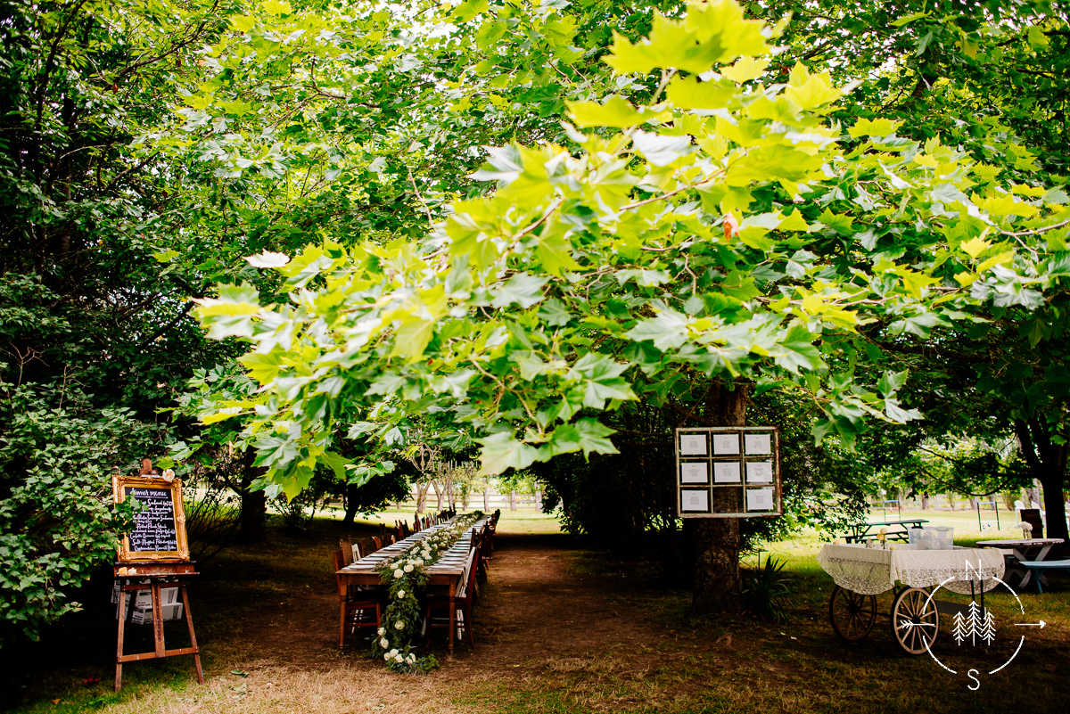 A wedding reception's dining table under a tent of trees in the Seattle destination of Whidbey Island.