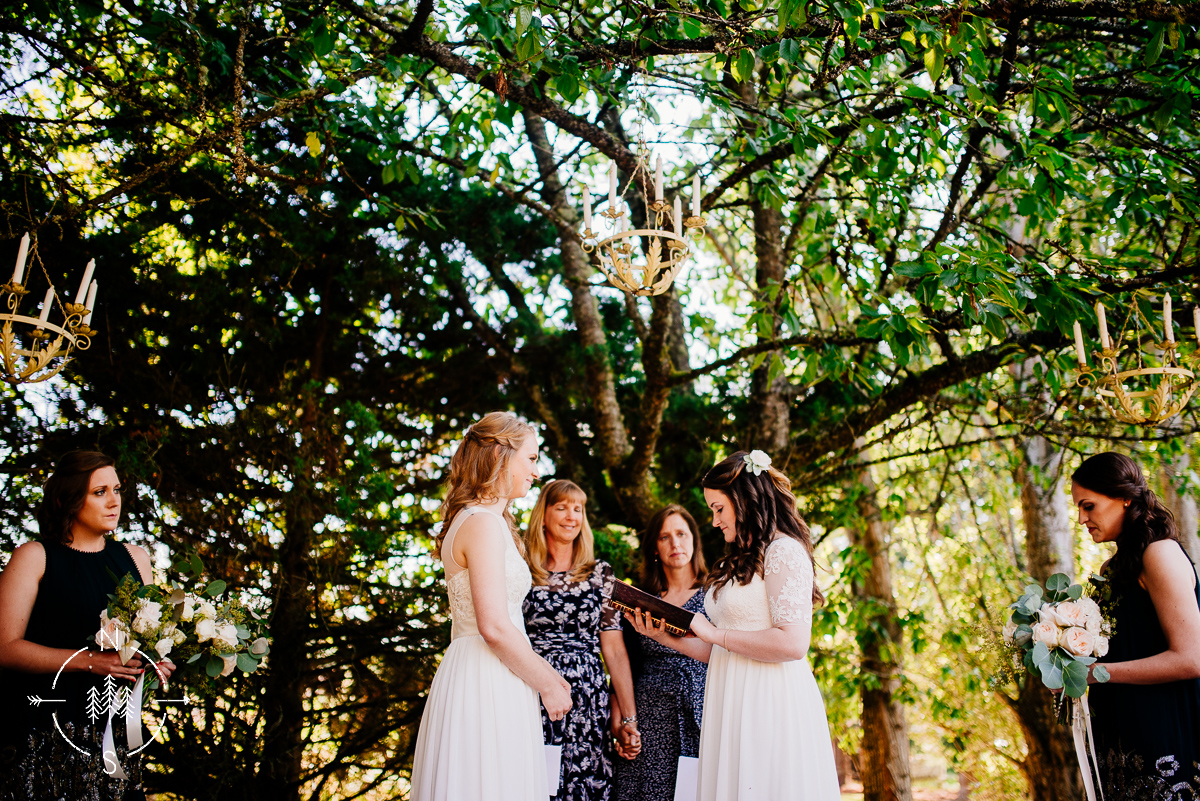 Same-sex wedding ceremony of two lesbian brides, under trees and with chandeliers.