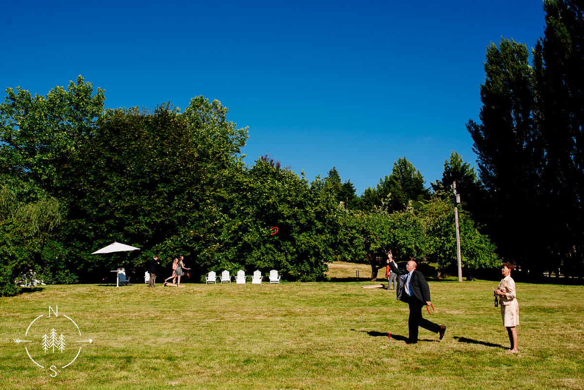 Wedding guests play lawn games like horseshoes and corn hole on the open field at Wayfarer Farm in Whidbey Island, WA.