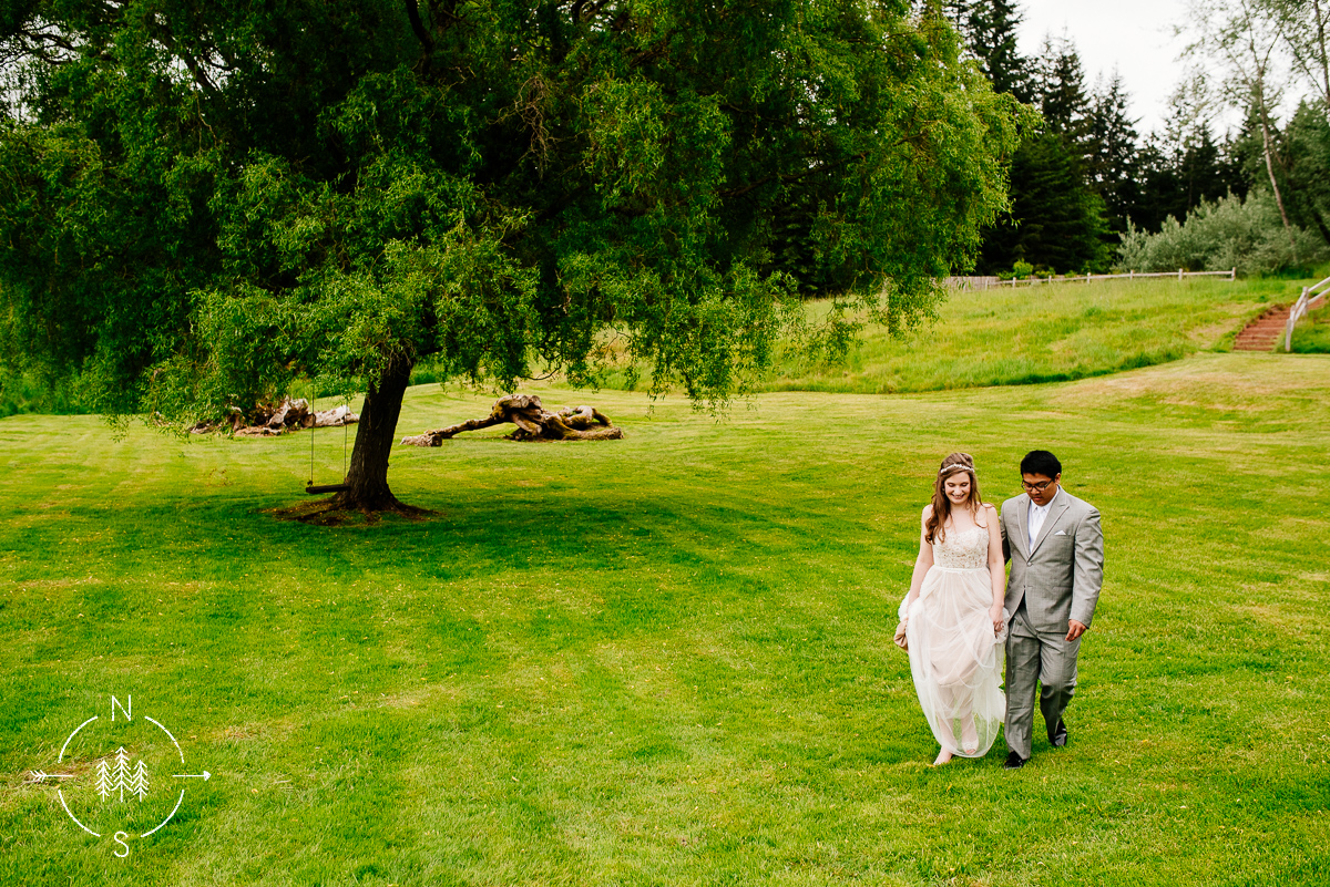 Wedding couple, husband and wife, walk along a field with a tree swing in the background.