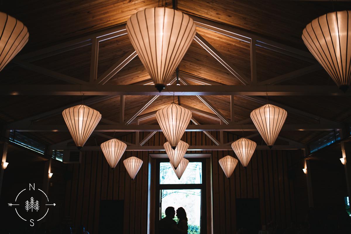 Modern lantern lights hang from inside a wedding reception barn in Whidbey Island.