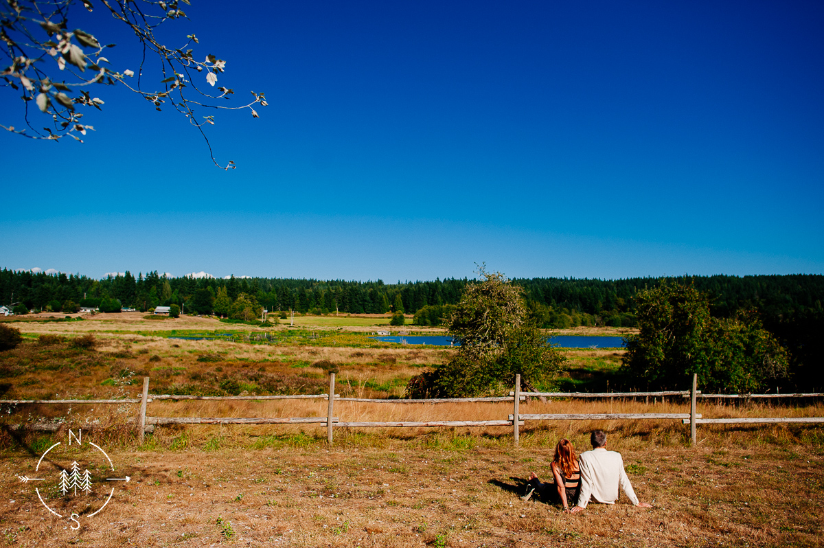 A couple sits on the grass and looks out over a lake on Whidbey Island.